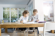 Two girls doing homework at table together using a tablet - MOEF00550