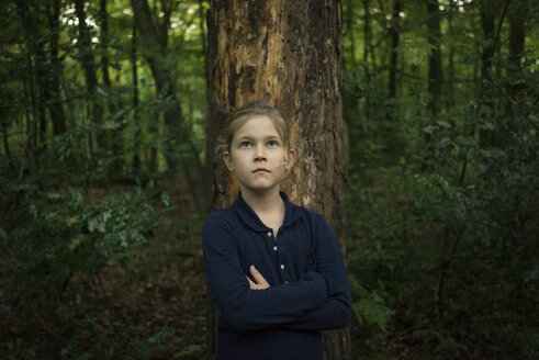 Portrait of confident girl standing at tree trunk in forest - MOEF00568