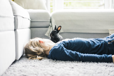 Girl lying with hare in living room - MOEF00577