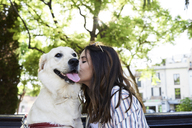 Young woman kissing her dog - IGGF00317