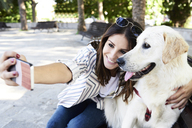 Happy young woman taking selfie with her dog - IGGF00323