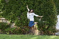 Happy young woman jumping in the air outdoors - IGGF00326