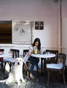 Young woman sitting in a coffee shop with her dog drinking a smoothie - IGGF00329