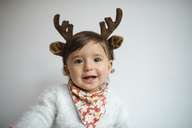 Portrait of laughing baby girl with reindeer antlers headband - GEMF01825