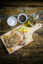 Roasted beefsteak with rosemary, and lemon on chopping board, salt, pepper and olive oil - GIOF03701