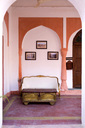India, Rajasthan, Alwar, Heritage Hotel Ram Bihari Palace, Corridor with sofa and old table - NDF00716