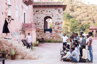India, Rajasthan, Alwar, Heritage Hotel Ram Bihari Palace, female tourist photographing employess - NDF00719