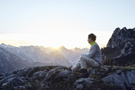 Austria, Tyrol, Rofan Mountains, hiker sitting on rocks at sunset - RBF06226