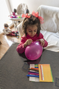 Little girl painting balloon, her little brother in the background - JASF01849