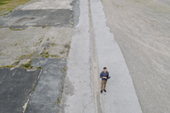 Young businessman using laptop in solitude, quadcopter view - KNSF03239