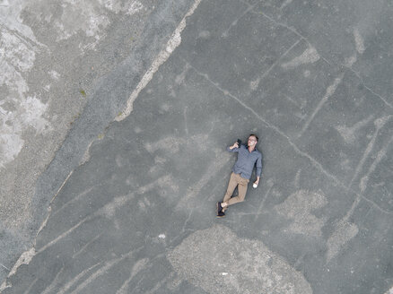 Young businessman with coffee to go lying on tarmac using mini tablet, quadcopter view - KNSF03242