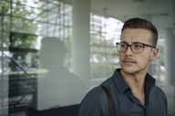 Portrait of pensive young businessman wearing glasses - KNSF03248
