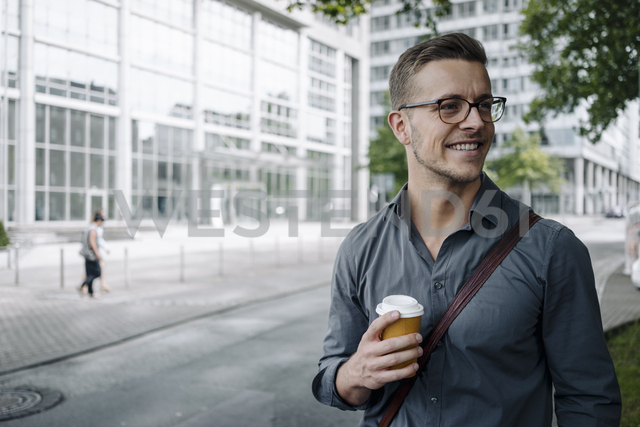 Portrait of smiling young businessman with coffee to go - KNSF03257