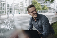 Portrait of laughing young businessman with laptop outdoors - KNSF03263