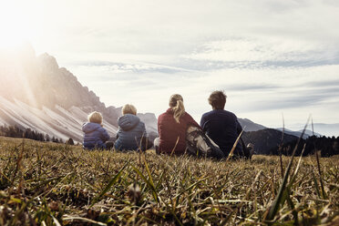 Italy, South Tyrol, Geissler group, family hiking, sitting on meadow - RBF06236