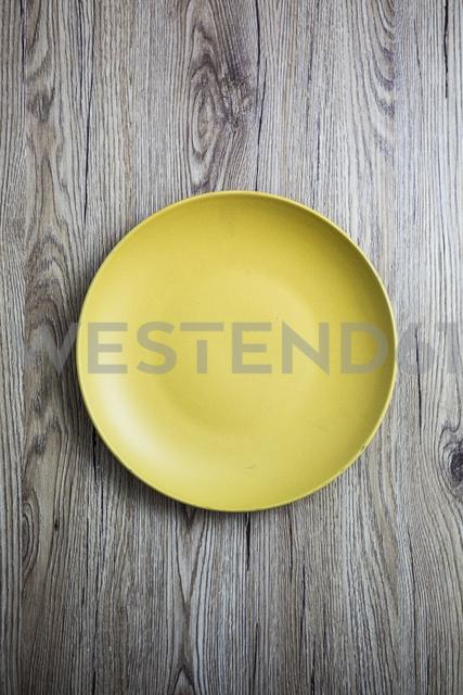 Empty yellow plate on wood - GIOF03709