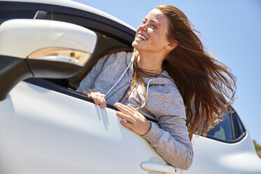 Young woman leaning out of window of a car - SRYF00578