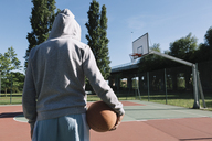 Man holding basketball, hoop in the background - ALBF00315