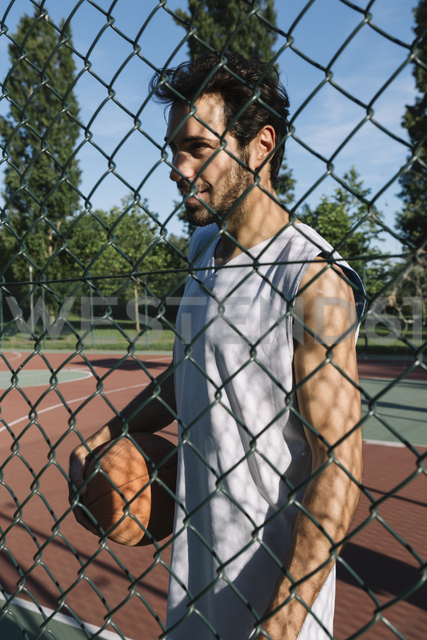 Man with basketball behind wire mesh fence - ALBF00339
