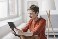 Smiling woman sitting on chair using tablet - KNSF03268
