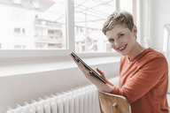 Portrait of smiling woman sitting on chair holding tablet - KNSF03271