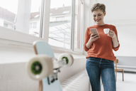Smiling woman with cell phone and espresso cup - KNSF03277