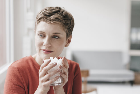Smiling woman holding glass full of sugar cubes - KNSF03280