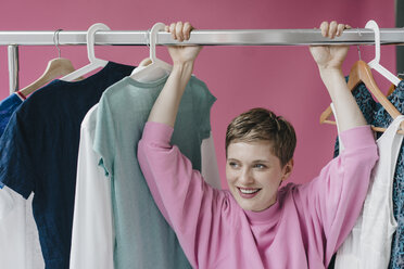 Portrait of smiling woman at clothes rail - KNSF03289