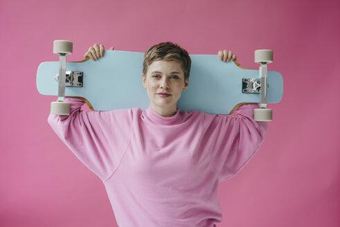 Portrait of woman in pink holding skateboard - KNSF03298