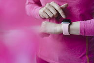 Close-up of woman in pink sportswear adjusting her smartwatch - KNSF03316