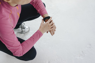 Woman in sportswear crouching wearing activity band - KNSF03325