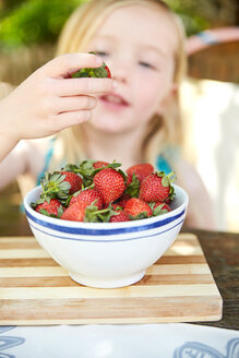 Girl eating stawberries form bowl - SRYF00588