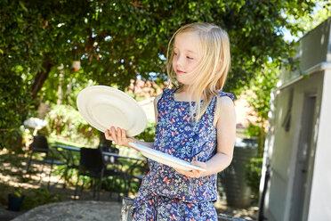 Blond girl holding plates in garden - SRYF00618