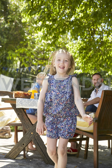 Portrait of laughing girl with parents in the background at garden table - SRYF00621