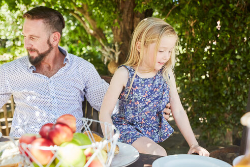 Girl with father sitting at garden table - SRYF00624