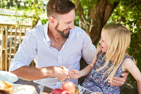 Happy girl with father sitting at garden table - SRYF00627