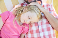 Girl relaxing with her father lying on a blanket - SRYF00648