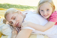 Mother and daughter relaxing lying on a blanket - SRYF00654