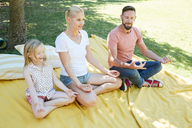 Family with girl practicing yoga on a blanket - SRYF00657