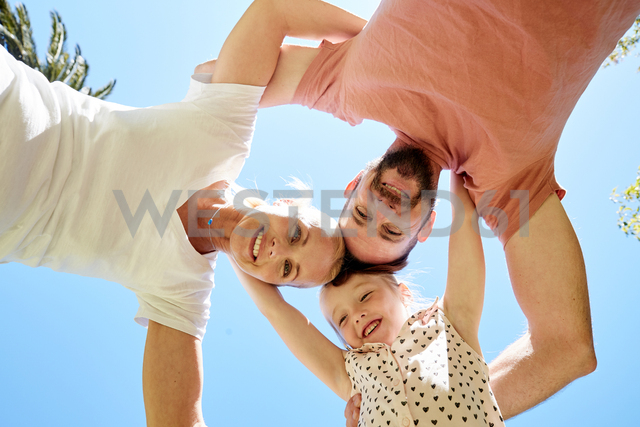 Portrait of happy family huddling under blue sky - SRYF00672