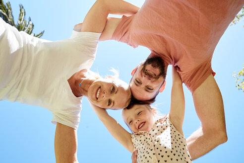 Portrait of happy family huddling under blue sky - SRYF00672