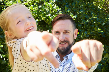 Portrait of happy father and daughter pointing their fingers - SRYF00678