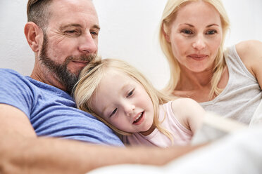 Happy family in bed reading book together - SRYF00693