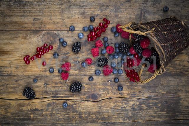Wickerbasket of various berries on wood - LVF06565