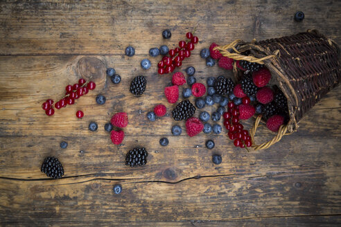Wickerbasket of various berries on wood - LVF06565