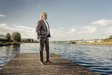Senior man standing on jetty at a lake - KNSF03328
