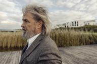 Portrait of serious senior man at lakeshore - KNSF03337
