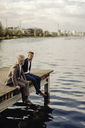 Two businessmen sitting on jetty at a lake - KNSF03343