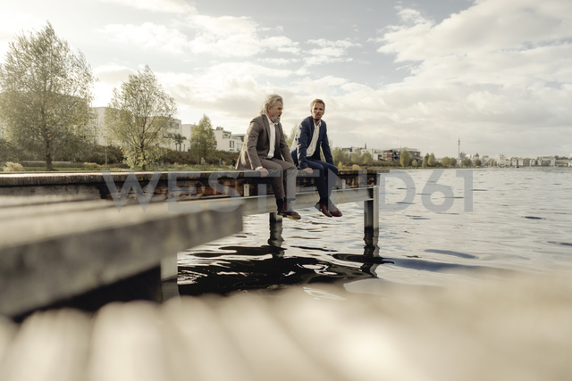 Two businessmen sitting on jetty at a lake - KNSF03346 - Kniel Synnatzschke/Westend61