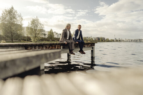 Two businessmen sitting on jetty at a lake - KNSF03346
